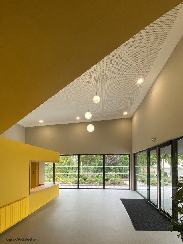 les jeux de volumes dynamiques contrastent avec le paysage paisible à travers les larges baies vitrées du hall